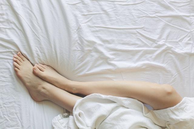 Človek ležiaci na bielom matraci zakrytí plachtou