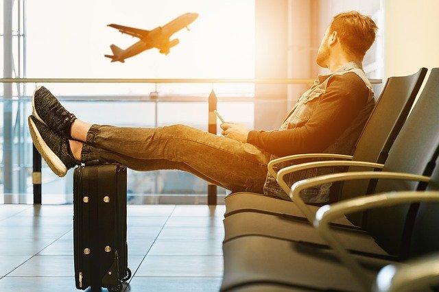 Muž sediaci v letiskovej hale sledujúci odlietajúce lietadlo