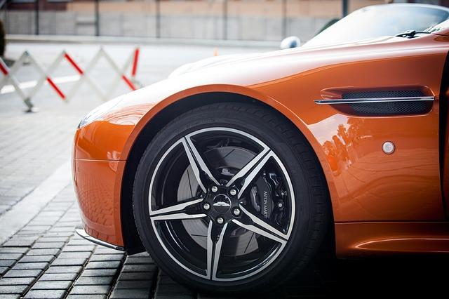 Oranžové auto stojí na ceste pri závore