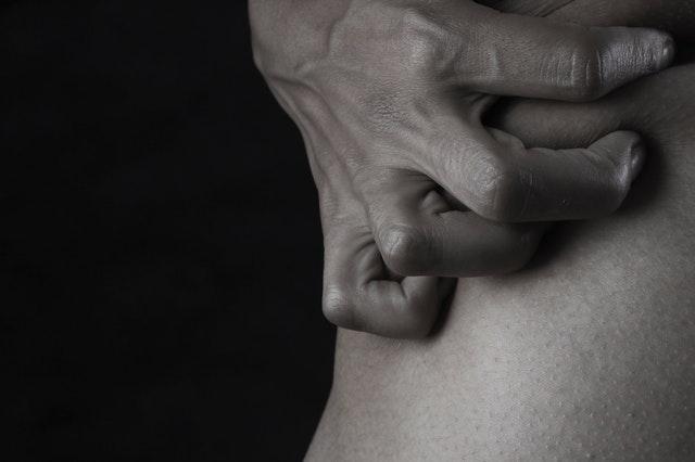 Človek si drží kožu rukou.jpg