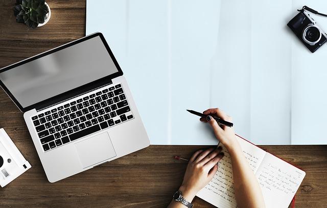 Pracovný stôl, na ktorom je notebook a veľký biely papier, na ktorý človek píše
