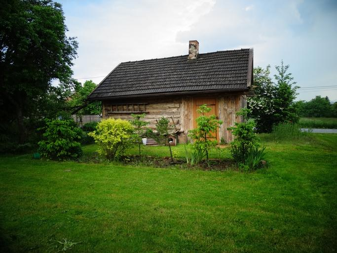 Drevená malá stavba postavená uprostred lúky, okolo ktorej sú zelené rastliny.jpg