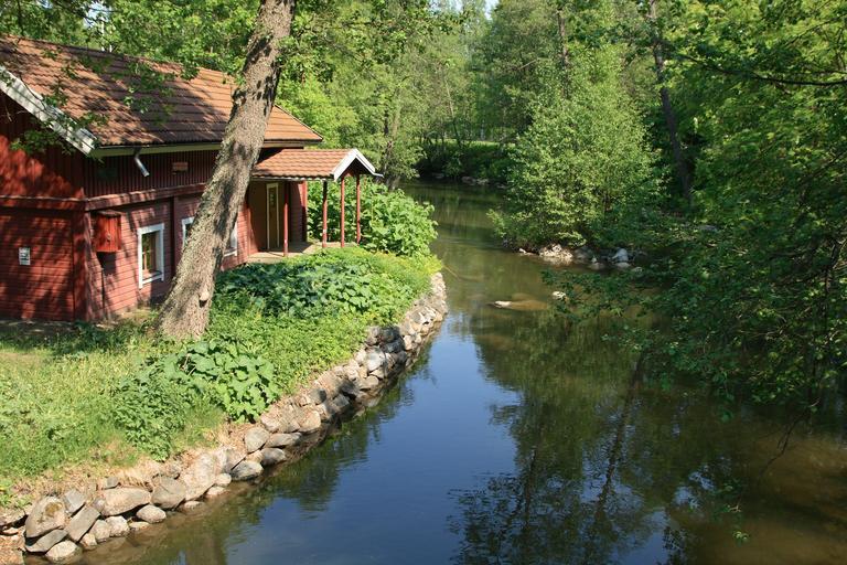 Podlhovastý nízky dom červenej farby na brehu rieky, medzi stromami.jpg