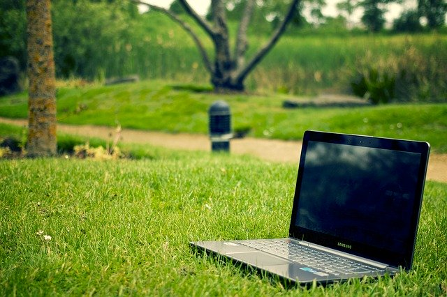 Tmavý notebook položený  na zelenom pokosenom trávniku.jpg
