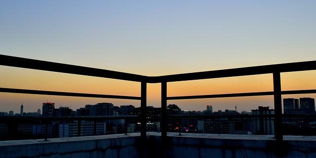 Tmavé zábradlie na terase, západ slnka nad mestom.jpg