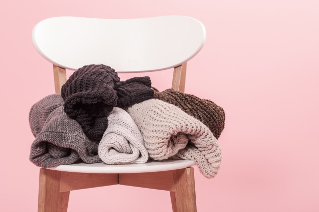 white-chair-with-stack-knitted-sweaters-pink-background_169016-3383